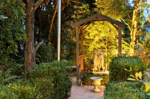 Three Graces statue in a garden arbour